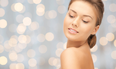 down lights: beauty, people, holidays, luxury and health concept - beautiful young woman face over lights background Stock Photo