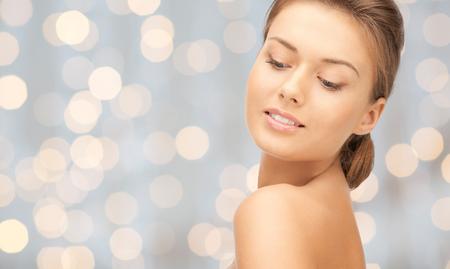 carita feliz: la belleza, la gente, las vacaciones, el lujo y el concepto de salud - cara hermosa mujer joven sobre el fondo de las luces