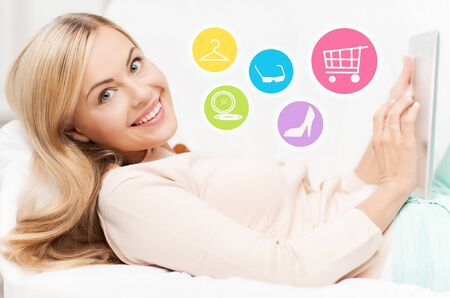 woman lying in bed: online shopping, sale, fashion and people concept - happy woman or housewife with laptop shopping online at home Stock Photo