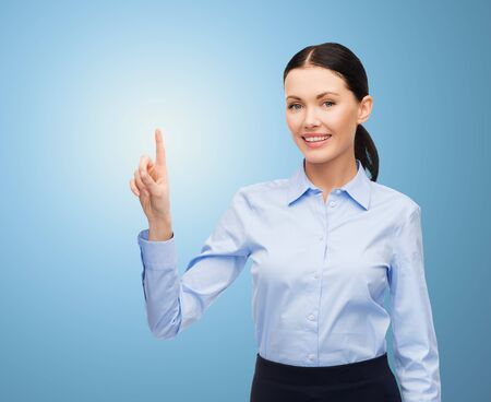 business, technology and people concept - businesswoman pointing finger to or touching something imaginary over blue background Stock Photo