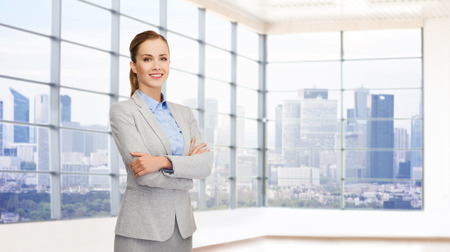 Realtor: business, people and education concept - smiling young businesswoman with crossed arms over office room background