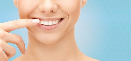 sonrisa: salud dental, la belleza, la higiene y la gente concepto - cerca de la sonriente cara de la mujer que señala a los dientes sobre fondo azul
