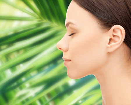 face female: health, people, eco and beauty concept - beautiful young woman face over green palm leaf background Stock Photo