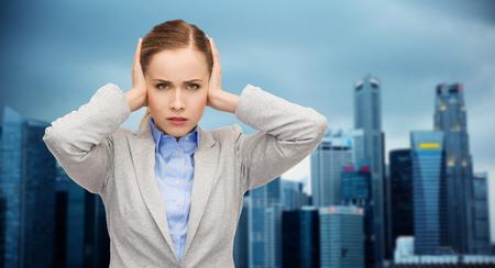 ruido: negocio, las emociones, el estrés, la presión y el concepto de la gente - empresaria destacó con los oídos cubiertos sobre el fondo de la ciudad
