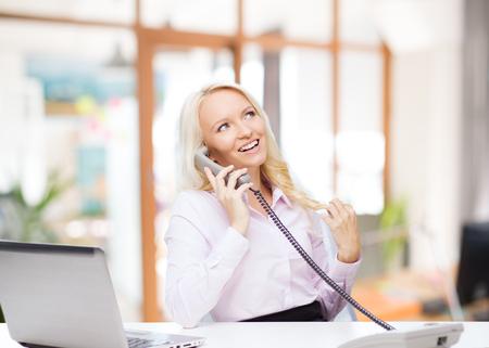 llamando: educación, los negocios, la comunicación y la tecnología concepto - la sonrisa de negocios o estudiante con llamadas ordenador portátil en el teléfono sobre el fondo sala de oficina