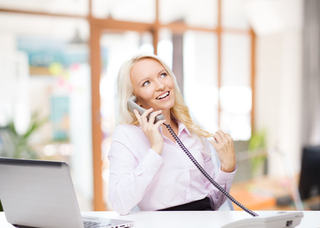 calling on phone: education, business, communication and technology concept - smiling businesswoman or student with laptop computer calling on phone over office room background Stock Photo