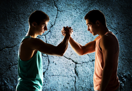 man power: sport, competition, strength and people concept - two young men arm wrestling over concrete wall background Stock Photo