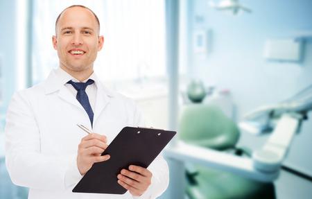 의학, 직업, stomatology 및 건강 관리 개념 - 클립 보드와 남성 치과 의사 웃는 의료 사무실 배경