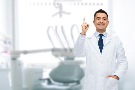 odontologo: cuidado de la salud, profesión, gesto, estomatología y el concepto de la medicina - varón sonriente dentista de mediana edad que destaca el dedo sobre fondo consultorio médico