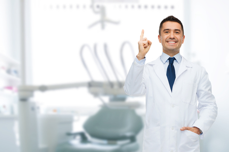 clinics: healthcare, profession, gesture, stomatology and medicine concept - smiling male middle aged dentist pointing finger up over medical office background