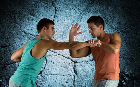 artes marciales: deporte, competencia, fuerza y ??concepto de la gente - los hombres jóvenes luchando mano a mano sobre fondo muro de hormigón