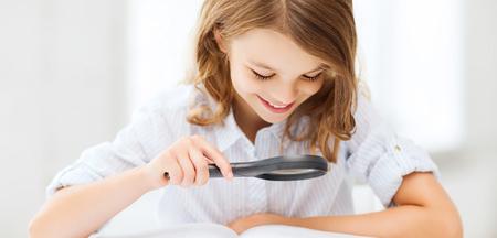 lupa: la educación y la escuela concepto - niña estudiante de la lectura del libro con la lupa en la escuela