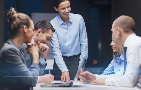女性の上司がオフィスでビジネス チームに話を笑顔 - ビジネス、技術、管理、人々 の概念
