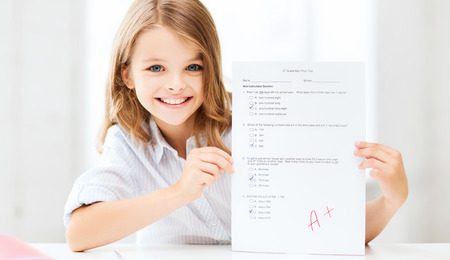education and school concept - little school girl with test and A grade at school Foto de archivo