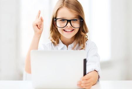onderwijs: Onderwijs, school, technologie en internet concept - kleine student meisje in zwarte bril met tablet pc computer en vinger op school Stockfoto