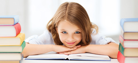 girl: education and school concept - smiling little student girl with many books at school Stock Photo