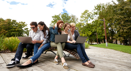 laptop computers: summer, communication, technology , education and teenage concept - group of students or teenagers with laptop computers at park or campus Stock Photo