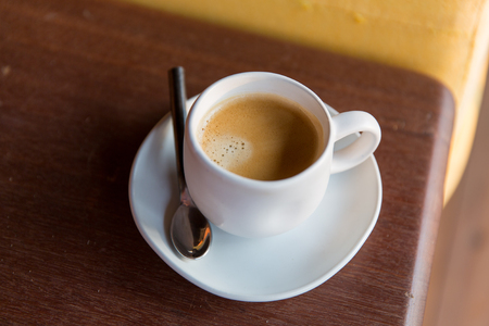 drinks, energetic, morning and caffeine concept - cup of black coffee with spoon and saucer on table Imagens