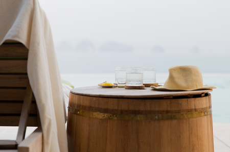 travel, tourism, summer vacation, drinks and refreshment concept - glasses of water with hat on barrel and lounge at hotel beach