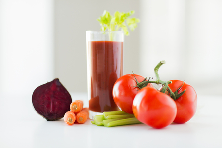 tomato cocktail: healthy eating, organic food and diet concept - close up of fresh juice glass and vegetables on table Stock Photo