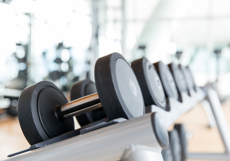 exercise equipment: sport, fitness, weightlifting and health care concept - close up of dumbbells in gym