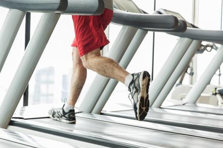 piernas hombre: deporte, fitness, la tecnología y el concepto de la gente - cerca de las piernas masculinas que se ejecutan en cinta rodante en el gimnasio