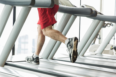 bodycare: sport, fitness, technology and people concept - close up of male legs running on treadmill in gym