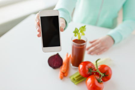 healthy eating, technology, diet and people concept - close up of woman hands with smartphone, tomato juice and vegetables