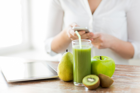 woman eating fruit: healthy eating, technology, diet and people concept - close up of woman hands holding smartphone with tablet pc, fruits and fresh juice sitting at table Stock Photo