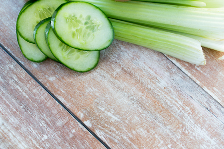cucumber: diet, vegetable food and objects concept - close up of cucumber slices and celery