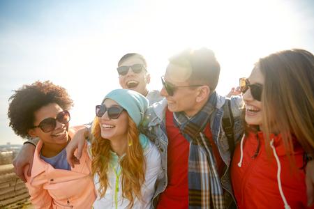 människor: turism, resa, folk, fritid och teenage koncept - grupp lyckliga vänner i solglasögon kramar och skrattar på stadsgatan