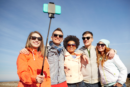 tourism: tourism, travel, people, leisure and technology concept - group of smiling teenage friends taking selfie with smartphone and monopod on city street