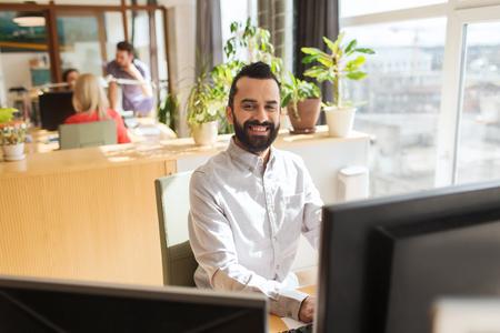 obrero trabajando: negocio, puesta en marcha y la gente concepto - hombre de negocios feliz o creativo oficinista de sexo masculino con el ordenador