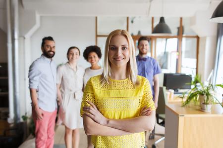 entreprise, le démarrage, les gens et concept d'équipe - jeune femme heureuse sur l'équipe créative dans le bureau