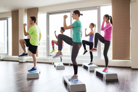 aerobics class: fitness, sport, training, aerobics and people concept - group of people working out with steppers in gym
