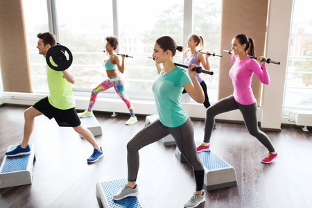 aerobic instructor: fitness, sport, training, gym and lifestyle concept - group of people exercising with barbell and bars in gym Stock Photo