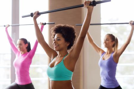 피트니스, 스포츠, 교육, 헬스 클럽 및 생활 양식 개념 - 체육관에서 바 함께 운동을하는 사람들의 그룹