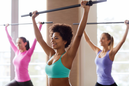 aerobic instructor: fitness, sport, training, gym and lifestyle concept - group of people exercising with bars in gym