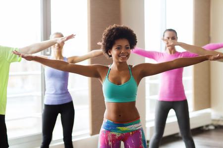 gente bailando: fitness, deporte, la danza y el estilo de vida concepto - grupo de gente sonriente con zumba baile entrenador en el gimnasio o estudio