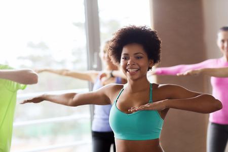 фитнес: фитнес, спорт, танцы и образ жизни концепция - группа людей, улыбаясь с тренером танцевальной Zumba в тренажерном зале или студии Фото со стока