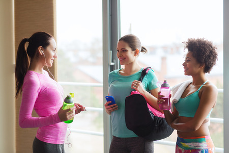 women talking: fitness, sport, training and lifestyle concept - group of happy women with bottles of water, smartphone and bag talking in gym