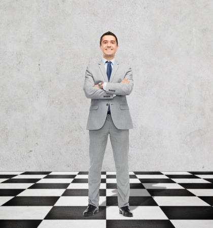 floor standing: business, people and strategy concept - happy smiling businessman in suit standing on checkerboard pattern floor over gray background