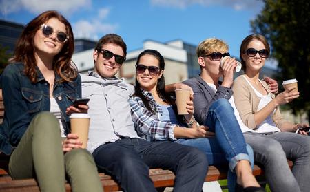 Vacaciones de verano, de la amistad, de ocio y concepto de adolescente - grupo de estudiantes felices o adolescentes que cuelgan hacia fuera y tomar café en el campus o parque Foto de archivo - 45905014