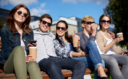 zomervakantie, vriendschap, vrije tijd en tiener concept - groep van gelukkige studenten of tieners opknoping uit en drinken koffie op de campus of park