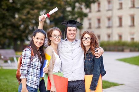 graduacion: la educación, la escuela, la amistad, la graduación y la gente concepto - grupo de estudiantes adolescentes felices con las carpetas de la escuela secundaria