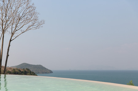 runaway: travel, vacation, tourism and luxury concept - beautiful view from infinity edge pool to sea