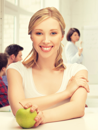 lecturer: picture of beautiful girl with green apple at school Stock Photo