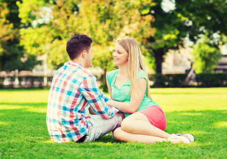couple talking: smiling couple sitting on grass and talking in park Stock Photo