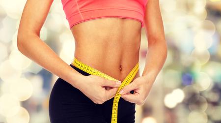 cintura perfecta: Cerca de las manos femeninas que miden la cintura con cinta métrica