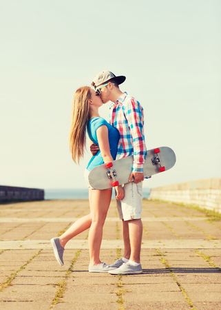 love kissing: couple with skateboard kissing outdoors
